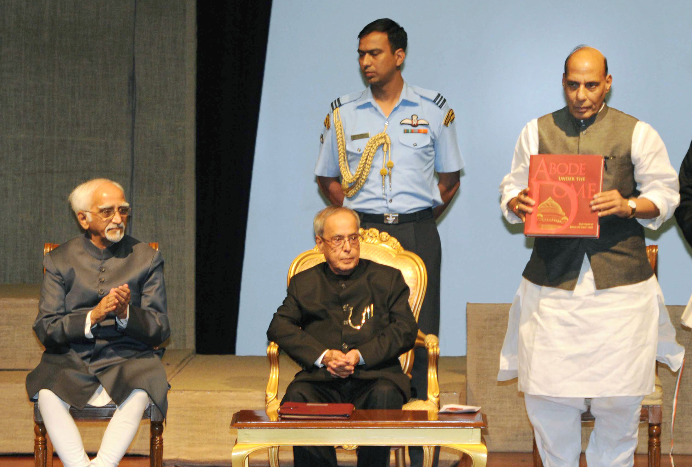 """The President, Shri Pranab Mukherjee, the Vice President, Shri Mohd. Hamid Ansari and the Union Home Minister, Shri Rajnath Singh, during the release of the book titled """"Abode under the Dome"""", at Rashtrapati Bhavan, in New Delhi on July 24, 2015."""