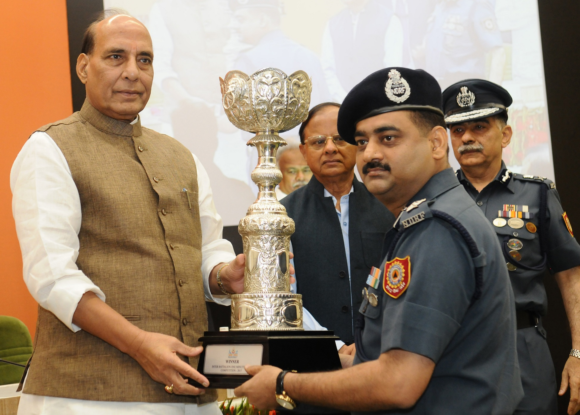 """The Union Home Minister, Shri Rajnath Singh distributing award of trophies to the winners of NDRF Inter Battalions Professional competition, at the inauguration of the National Level Conference on """"Capacity Building of SDRFs-2017"""", organised by the NDRF, in New Delhi on June 06, 2017. The Additional Principal Secretary to the Prime Minister, Dr. P.K. Mishra and the DG, NDRF, Shri R.K. Pachnanda are also seen."""