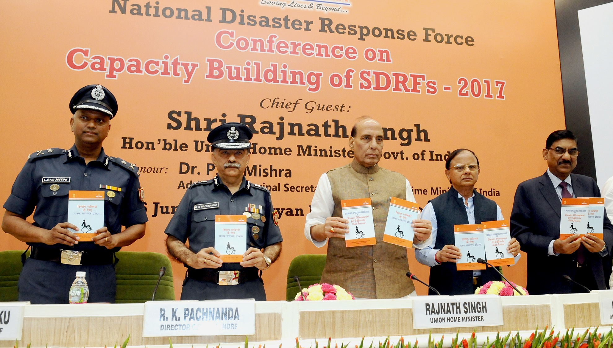 """The Union Home Minister, Shri Rajnath Singh releasing the 'Standard Operating Procedure on Disaster Management for Differently Abled Persons', at the inauguration of the National Level Conference on """"Capacity Building of SDRF-2017"""", organised by the NDRF, in New Delhi on June 06, 2017. The Additional Principal Secretary to the Prime Minister, Dr. P. K. Mishra and the DG, NDRF, Shri R.K. Pachnanda are also seen."""