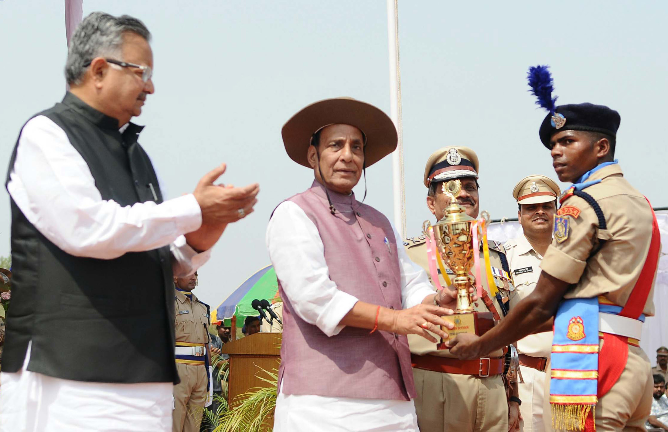 The Union Home Minister, Shri Rajnath Singh presenting the trophies, on the occasion of the Passing Out Parade of the 'Bastariya Battalion' of CRPF, at Ambikapur, in Chhattisgarh on May 21, 2018.  	The Chief Minister of Chhattisgarh, Dr. Raman Singh is also seen.